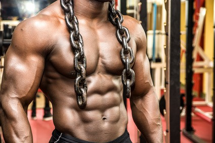 Attractive hunky black male bodybuilder doing bodybuilding pose in gym with iron chains over shoulders